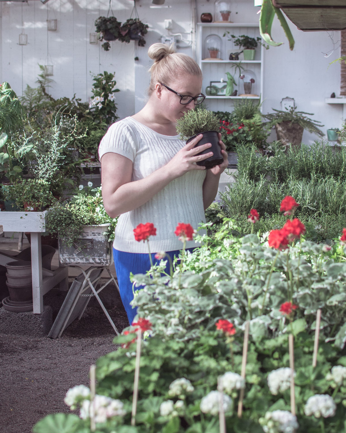 Blonde woman smelling flowers in a greenhouse